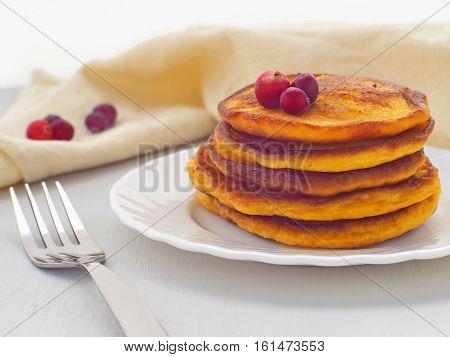 Pumpkin pancakes with fresh cranberries. Fresh homemade flapjacks. Thanksgiving treat. Horizontal.