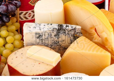 Various type of cheese and grapes closeup picture.