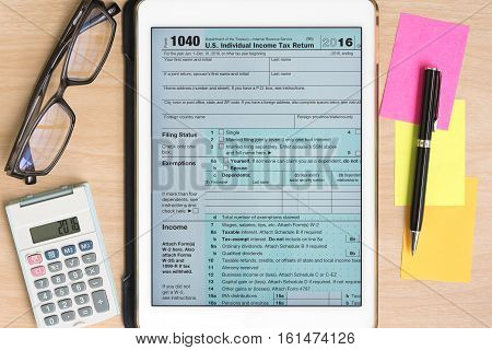 US Tax form 1040 in tablet with calculator and pen on sticky note on wooden desk