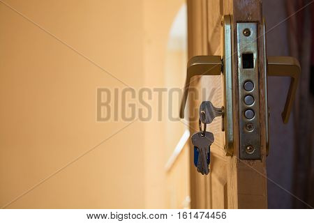 Safe lock mechanism in the open home wood door. Keys in the keyhole.