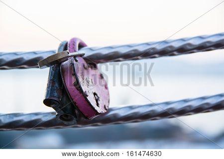 Few wedding locks hanging on a handrail. Symbol of marriage.