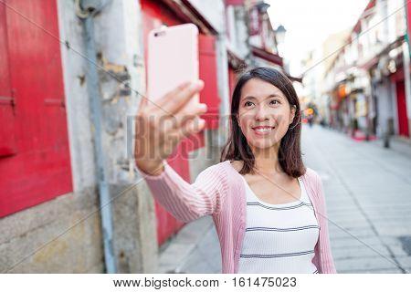 Woman taking selfie by mobile phone in Macau city
