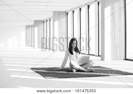 Young businesswoman with laptop sitting on turf in empty office