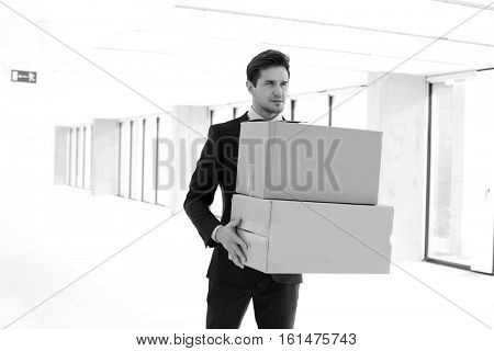 Young businessman carrying cardboard boxes in new office