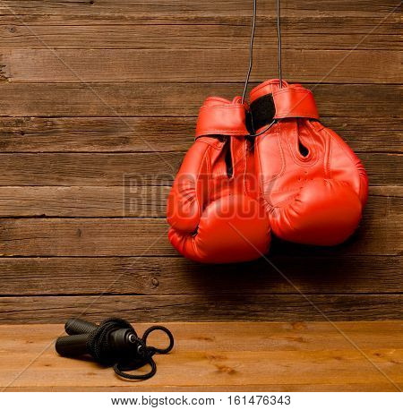 Two red boxing gloves hung on a wooden brown background skipping rope empty space