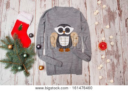 Gray sweater with an owl on a wooden background. Fur-tree branch with Christmas decorations stocking garland gift