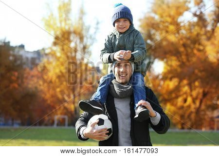 Father and son with ball on soccer pitch