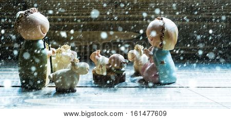 Christmas and Jesus birth figurines of holy virgin Mary Joseph newborn child with few sheep standing on wooden background under white snow and snowflakes