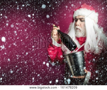 New year man with serious face has long white beard and hair in red santa claus christmas coat and hat holding silver pail and wine bottle on purple background under snow and snowflakes copy space