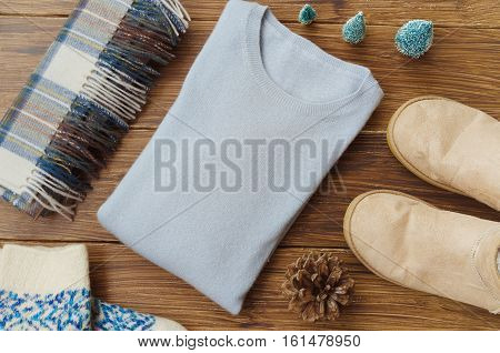 Flat lay. View of winter knitted clothes . Cashmere sweater ugg boots wool square scarf and mittens little Christmas tree and natural fir cone on wooden background. Concept for Winter and Christmas. Copy space.