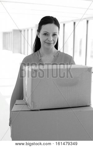 Portrait of mid adult businesswoman carrying cardboard boxes in new office