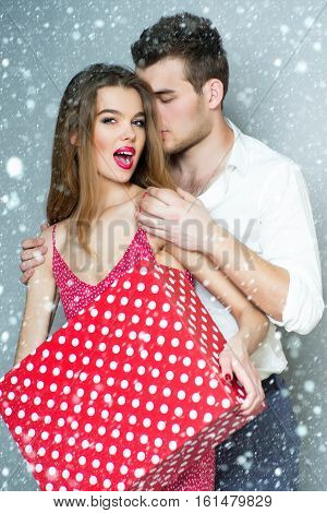 sexy cute young new year couple standing close to each other embraces holding big spotted red present christmas or xmas box under snow and snowflakes/ smiling pretty girl and man