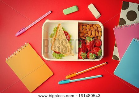 Lunch box with food and stationery on red background, top view