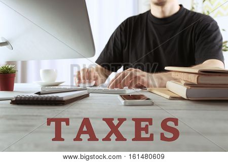 Tax concept. Business man at office, closeup. Word TAXES on background
