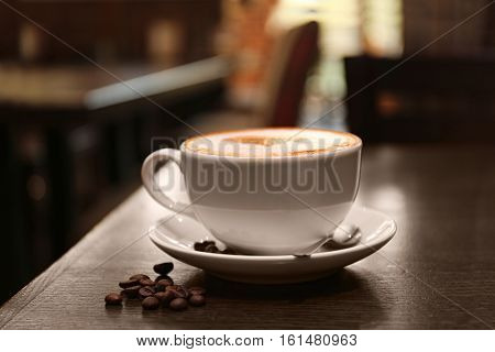Cup with hot tasty coffee on wooden table in cafe, close up view
