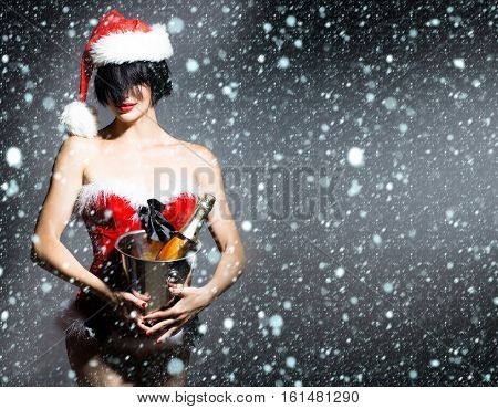 young sexy new year woman or girl with red lips on pretty face in christmas santa claus hat and holiday costume holds metallic pail with wine bottle on grey background under snow and snowflakes