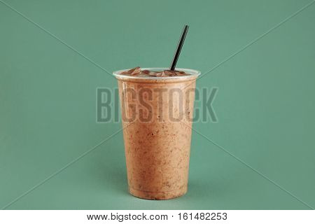 Tasty chocolate milkshake in plastic cup on green background