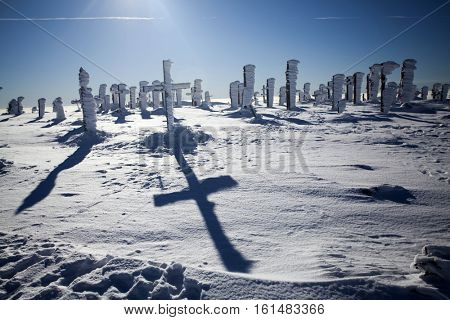 Frozen crosses in winter landscape