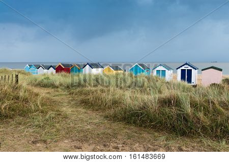 A line of colourful beach huts next to the sand dunes at Southwold Suffolk
