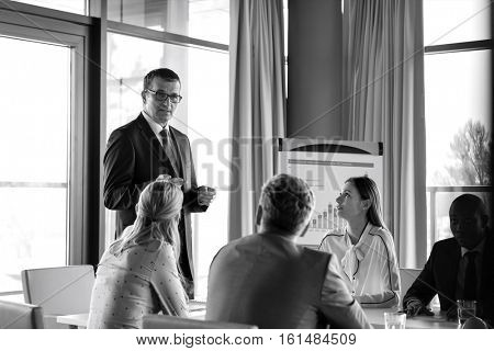 Mature businessman having discussion with colleagues in board room