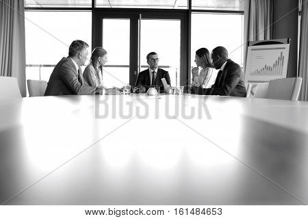 Multi-ethnic business people having discussion at conference table in office