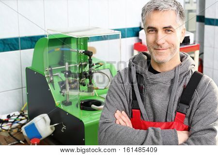 Injector tester. Car mechanic in the workshop. Auto mechanic workshop.