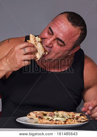 Big strong bodybuilder man eating pizza slice.