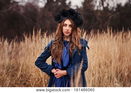 beautiful goth girl standing in an autumn field, wearing a blue coat and a blue satin dress with a black wreath on his head