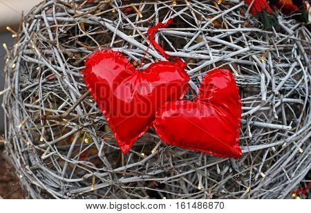 Two red hearts made of patent leather on a background of woven twigs