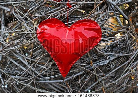 Red heart made of patent leather on a background of woven twigs