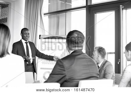 Young businessman giving presentation to colleagues in board room