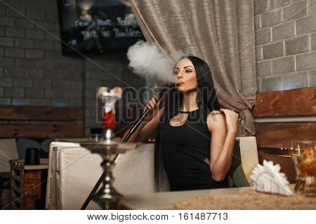 The Beautiful Girl Smokes A Hookah And Lets The Smoke. Woman Resting In A Bar