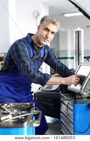 Engine diagnostics. Car mechanic, computer examination car. Car in diagnostic station, mechanic connected device