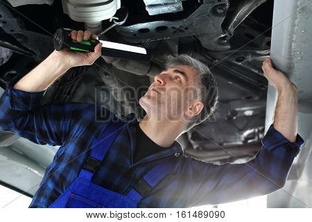 Vehicle inspection station, a car for technical inspection. Car repair shop, mechanic repairing a car. The car in the garage, the mechanic checks the status of the chassis.