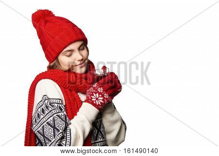 Closeup of young woman in warm winter clothing with cup of tea enjoying with closed eyes, on white background