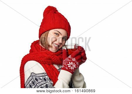 Closeup of young smiling woman in warm winter clothing with cup of tea on white background