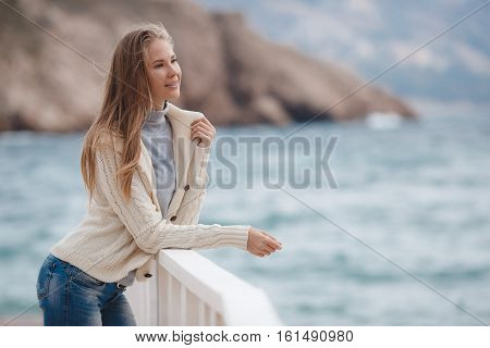 Young woman with long straight blond hair and gray eyes, dressed in a white knitted jacket, a gray turtleneck and blue jeans, spending time alone, standing on white wooden wharf near the blue sea on a background of mountains, enjoying the waves