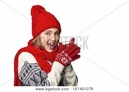 Closeup of excited emotional woman in warm winter clothing with cup of tea on white background