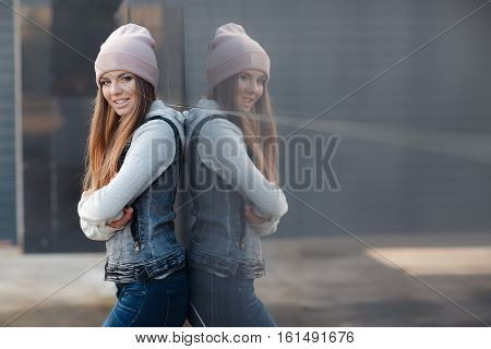 Young beautiful woman with model looks,beautiful makeup,pale pink lipstick,long red hair,big black eye lashes,blue eyes,wearing a light knitted sweater and denim vest,blue jeans and a pink sports hat posing on grey background in the city in the fall