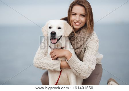 Beautiful young woman with long straight hair, light tan color, dressed in a white knitted sweater with a big collar beige, light make-up and gray eyes, spends time sitting on the beach with his friend, a pet, a dog breed golden retriever
