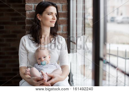 Beautiful brunette woman with thick long hair,sitting on the windowsill near the window,dressed in white pants and a white t-shirt,lulling her newborn son,holding him in her arms,the baby keeps the pacifier in your mouth blue