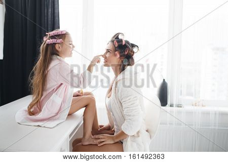 Mother and young daughter to make yourself a beautiful hairstyle,white bedroom near the window, helping each other,wind hair onto large pink curlers,both dressed in bright dressing gowns and bright t-shirts,girl sitting on a white table
