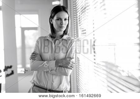 Portrait of confident young businesswoman with arms crossed leaning against window in office