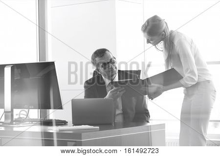 Young businesswoman showing file to businessman at desk in office
