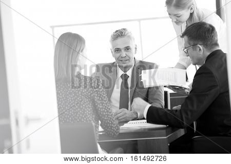Portrait of confident mature businessman with colleagues in meeting room
