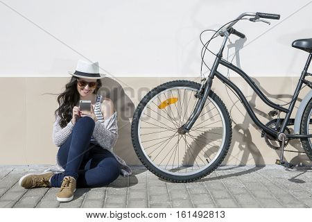 Young cheerful woman in sunglasses and hat sitting nearby bike and using device. Lanzarote Gran Canaria Spain.
