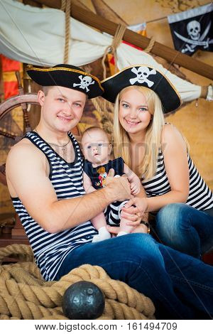 Happy family, mother, father and little son in pirate hats and vests.