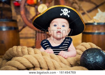 Newborn baby boy in a pirate hat is on the ropes. The interior of the ship's deck.