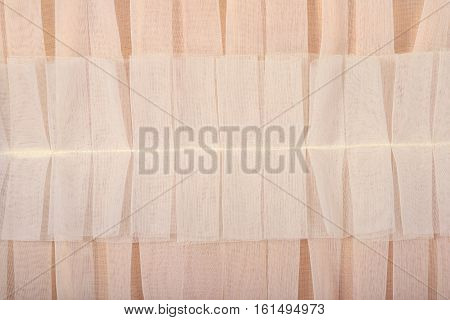 Beige pleated transparent caprone cloth as background texture close up