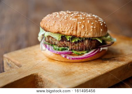 Classic american fast food background. Burger whole grain bun with grilled on barbecue meat and onions on wooden cutting board. Hamburger with fresh vegetables composition.